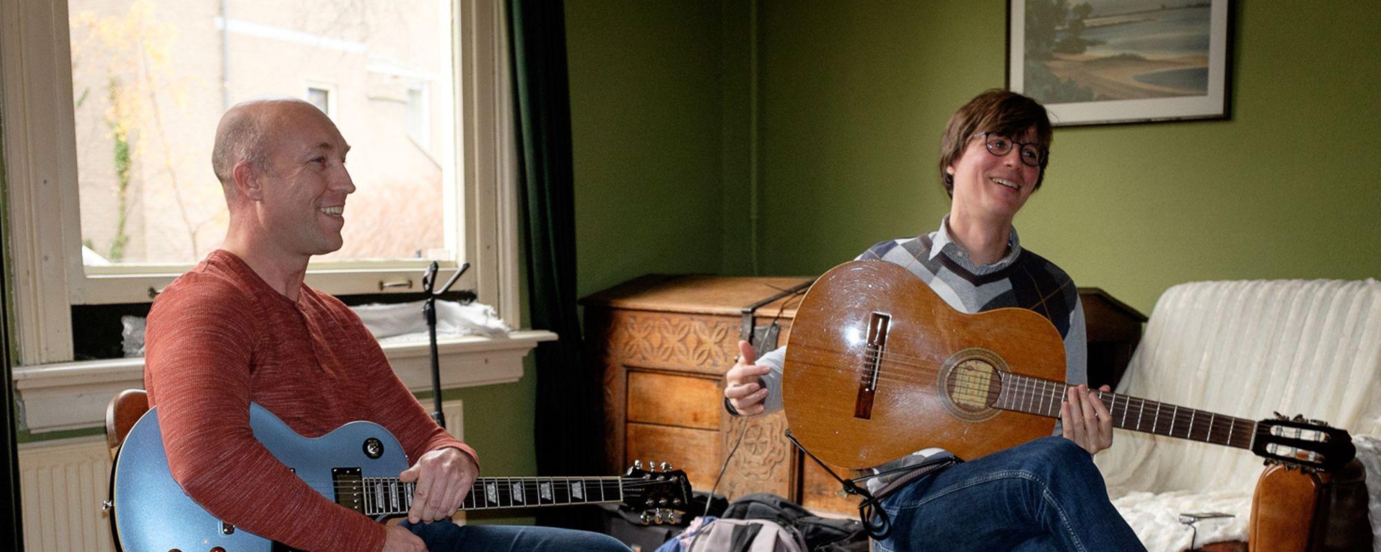 Volwassen leerling en leraar op voorspeelmiddag gitaar