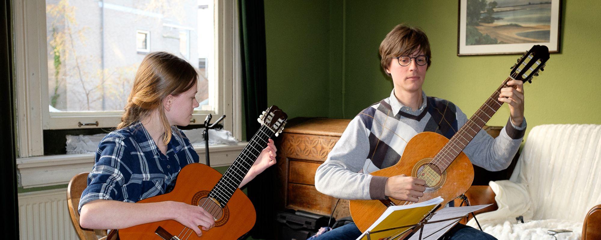Leerling en leraar spelen samen gitaar